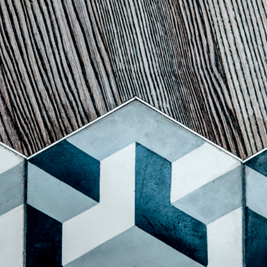 Hexagonal cement tiles with geometric shapes on wood floor