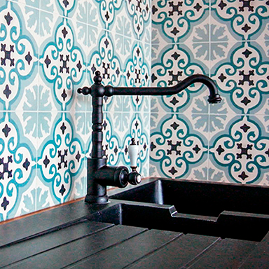 Encaustic cement tile backsplash in rustic blue kitchen